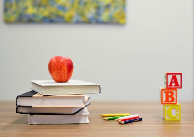 Pile of books on desk for graduate teaching opportunities