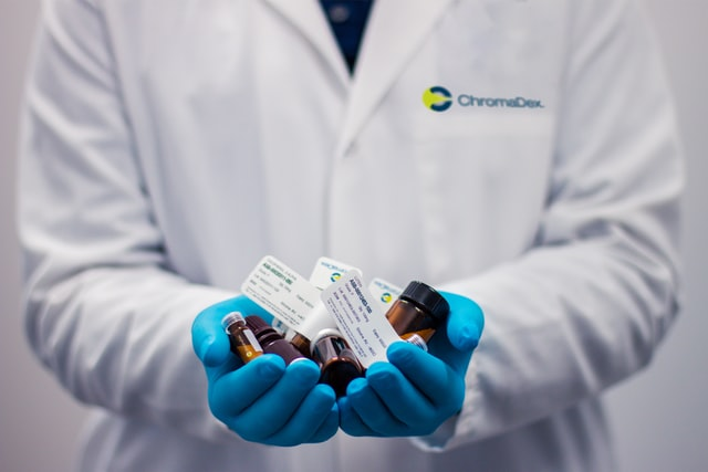 A person in a lab coat holding medication
