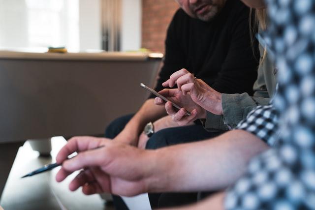 Three people discussing risk management graduate salaries