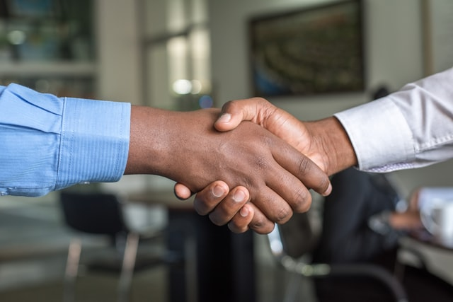 Two people shaking hands after being accepted onto a sales graduate scheme