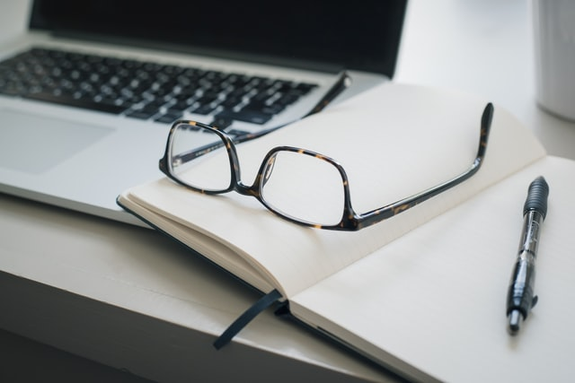 Laptop with glasses on notepad ready to search for marketing salary expectations